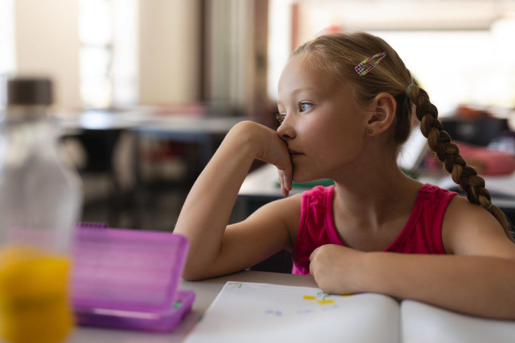 Close-up of distracted student leaning on desk and looking away in classroom of elementary school